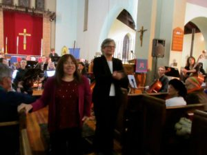 """Composer Peri Mauer takes a bow alongside Patricia Glunt, conductor, after the premiere of her piece """"All Along the Heights"""", composed for the Jackson Heights Orchestra."""